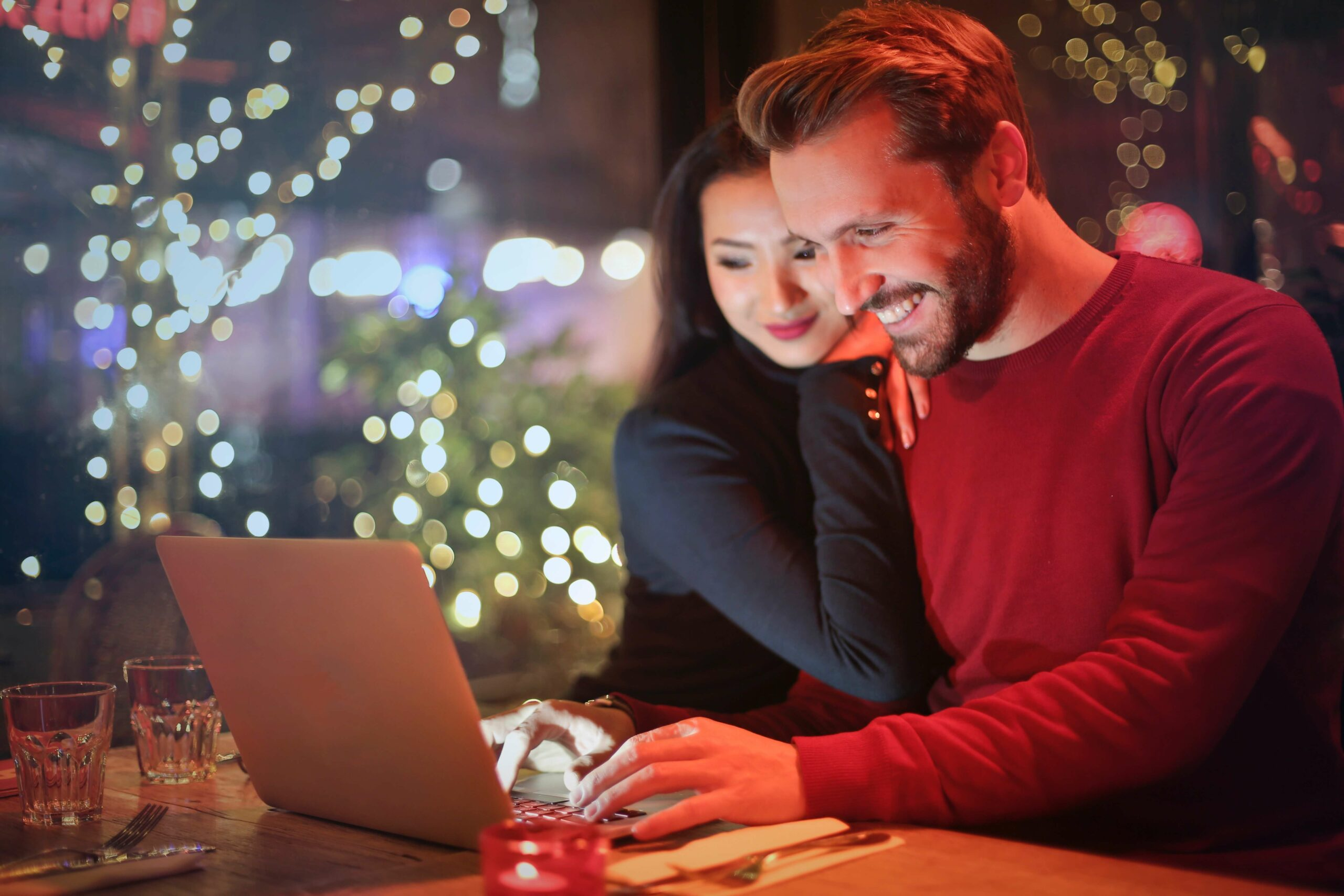 man and woman smiling at a computer in front of a Christmas tree